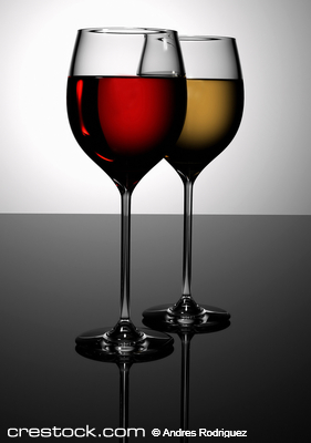 glasses of red and white wine on a black table...
