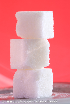 Close-up of three sugar cubes standing on top ...